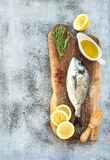 Fresh uncooked dorado or sea bream fish with lemon, herbs, oil and spices on rustic wooden board over grunge backdrop Stock Photo