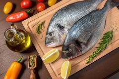 Fresh uncooked dorado or sea bream fish with lemon. Herbs, oil, vegetables and spices on wooden board over dark backdrop, top view Stock Photography