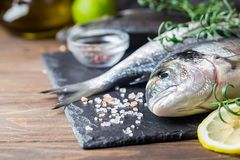Fresh uncooked dorado. Or sea bream fish with lemon slices, spices and herbs. Mediterranean cuisine. Top view Royalty Free Stock Photos
