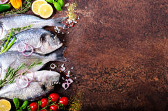Fresh uncooked fish, dorado, sea bream with lemon, herbs, vegetables and spices on rustic background. Top view. Fresh uncooked fish, dorado, sea bream with Stock Photo