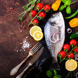 Fresh uncooked fish, dorado, sea bream with lemon, herbs, vegetables and spices on rustic background. Top view. Fresh uncooked fish, dorado, sea bream with Stock Image