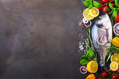 Fresh uncooked fish, dorado, sea bream with lemon, herbs, vegetables and spices on rustic background. Top view. Free space for you. Fresh uncooked fish, dorado Stock Photo