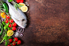 Fresh uncooked fish, dorado, sea bream with lemon, herbs, vegetables and spices on rustic background. Top view. Free space for you. Fresh uncooked fish, dorado Stock Photos
