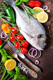Fresh uncooked fish, dorado, sea bream with lemon, herbs, vegetables and spices on rustic background. Top view. Free space for you. Fresh uncooked fish, dorado Royalty Free Stock Images