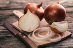 Fresh uncooked onion and onion cuts on chopping board Stock Photography