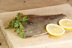 Fresh uncooked plaice. Fillet of plaice on cutting board with garnish Stock Images