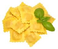Fresh Uncooked Ravioli Pasta. Fresh uncooked Italian ravioli pasta with basil herb garnish, isolated on a white background Royalty Free Stock Photography