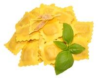 Fresh Uncooked Ravioli Pasta. Fresh uncooked Italian ravioli pasta with basil herb garnish, isolated on a white background Royalty Free Stock Photo
