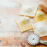 Fresh uncooked ravioli and rolling pin Royalty Free Stock Images