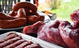 Fresh uncooked red meat, sausages and meatballs on the wooden table ready to be cooked on the outdoor fire grill. Barbecue  in the royalty free stock photo