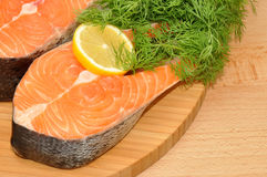 Fresh Uncooked Salmon Steaks. Two fresh raw pink salmon steaks with lemon slice and dill herb on a wooden cutting board Stock Photos