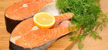 Fresh Uncooked Salmon Steaks. Two fresh raw pink salmon steaks with lemon slice and dill herb on a wooden cutting board Royalty Free Stock Photos