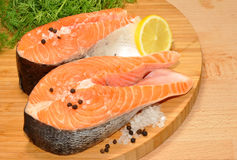 Fresh Uncooked Salmon Steaks. Two fresh raw pink salmon steaks with lemon slice and dill herb on a wooden cutting board Stock Photography