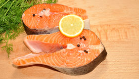 Fresh Uncooked Salmon Steaks. Two fresh raw pink salmon steaks with lemon slice and dill herb on a wooden cutting board Royalty Free Stock Photography