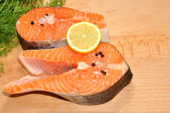 Fresh Uncooked Salmon Steaks. Two fresh raw pink salmon steaks with lemon slice and dill herb on a wooden cutting board Royalty Free Stock Image