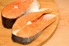 Fresh Uncooked Salmon Steaks. Two fresh raw pink salmon steaks on a wooden cutting board Royalty Free Stock Photos