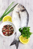 Fresh uncooked sea bream fish with lemon and aromatic herbs  Royalty Free Stock Images