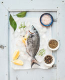 Fresh uncooked sea bream fish with lemon, herbs, ice and spices on rustic blue wooden board backdrop Stock Photos