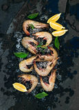 Fresh uncooked shrimps with lemon, herbs and spices on chipped ice over dark slate stone backdrop. Top view stock photo