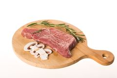 Fresh uncooked steak with pieces of mushroom and rosemary on wooden plate stock photo