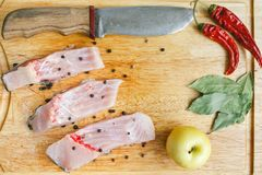 Uncooked pieces of silver carp fish with red chile pepper, bay leaf, apple, spices and knife on wooden board, top view. Royalty Free Stock Photo
