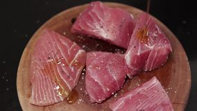 Fresh and uncooked tuna. Slow motion closeup. Closeup fresh fillet. Healthy food. Raw tuna with salt and papper. Big steaks tuna is poured olive oil. Tuna on a stock video