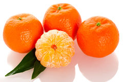 Fresh unpeeled orange mandarin citrus with green leafs and half Royalty Free Stock Images
