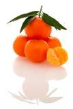 Fresh unpeeled orange mandarin citrus with green leafs and half Stock Photography
