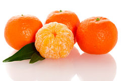 Fresh unpeeled orange mandarin citrus with green leafs and half Stock Photo