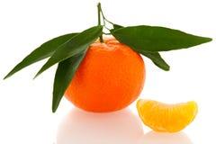 Fresh unpeeled orange mandarin citrus with green leafs and half Royalty Free Stock Photo