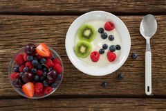 Fresh various fruits in bowl and plate. On wooden table Royalty Free Stock Photography