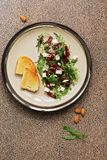 Fresh vegan dietary salad with beetroot, arugula, feta cheese, nuts and seeds over brown stone background. Top view, flat lay stock image