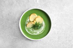 Fresh vegetable detox soup with croutons in dish on table. Top view stock photography