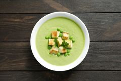 Fresh vegetable detox soup made of green peas. With croutons in dish on wooden background, top view stock photography