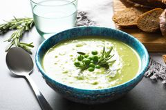 Fresh vegetable detox soup made of green peas in dish served. On table stock image