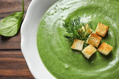 Fresh vegetable detox soup made of spinach with croutons in dish on table. Closeup royalty free stock images