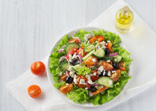 Fresh vegetable Greek salad with oil bottle, top view Stock Photo