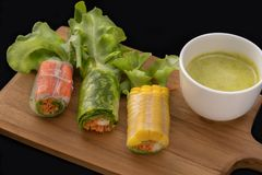 Fresh vegetable noodle spring roll with sauce on wooden tray,. Salad roll, On a black background. Diet or cook concept stock photography