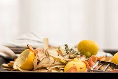 Fresh vegetable peels with peeler, knife and towel. Fresh vegetable scraps with peeler, knife and towel, house waste/compost management concept Royalty Free Stock Image