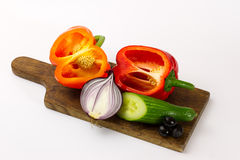 Fresh vegetable, peppers, cucumber, onion, olives. Red and orange peppers, cucumber, olives and red onion on the wooden breadboard Stock Image