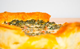 Fresh vegetable and prosciutto quiche tart close-up. Freshly baked vegetable and prosciutto crudo bacon quiche tart on a white plate and wood counter-top low DOF Stock Images
