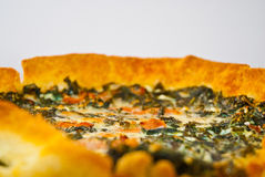 Fresh vegetable and prosciutto quiche tart low DOF. Freshly baked vegetable and prosciutto crudo bacon quiche tart on a white plate and wood counter-top low DOF Stock Photos