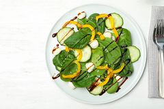 Fresh vegetable salad with balsamic vinegar served on wooden table, top view. Space for text royalty free stock image