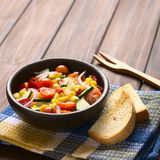 Fresh Vegetable Salad. Bowl of fresh vegetable salad made of sweet corn, cherry tomato, cucumber, red onion, red pepper, chives with toasted bread on the side Stock Photography