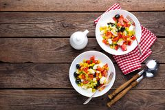 Fresh vegetable salad bowls of tomatoes, corn, pepper, olives, celery, green onion and feta cheese. Healthy food. Diet dinner or l. Unch menu. Salad plate on Stock Photos