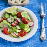 Fresh vegetable salad with cherry tomatoes, cucumber, radish and spinach on a white plate. On blue wooden surface Royalty Free Stock Images