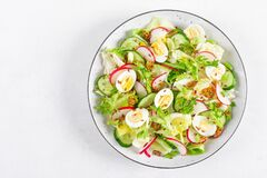 Fresh vegetable salad with cucumber, radish, lettuce and boiled eggs. Helathy food. Top view