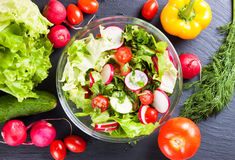 Fresh vegetable salad. Fresh salad of cucumbers, tomatoes, radishes and herbs. Top view Royalty Free Stock Image