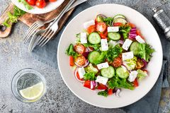 Fresh vegetable salad with feta cheese, fresh lettuce, cherry tomatoes, red onion and pepper. Top view royalty free stock image