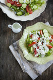 Fresh vegetable salad with feta cheese and tzatziki sauce. Served on plate Stock Photography